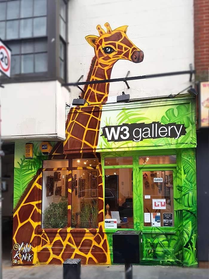 giraffe in the jungle street art mural on gallery facade