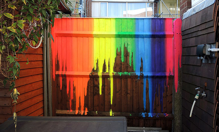 dripping rainbow neon street art mural painted on a garden fence