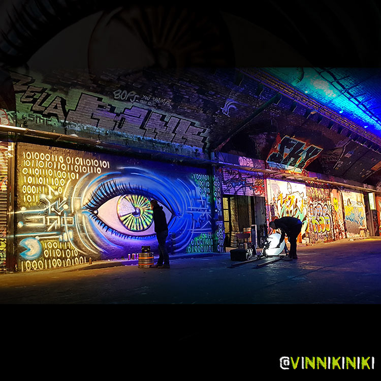 Black light reactive street art mural of an eye