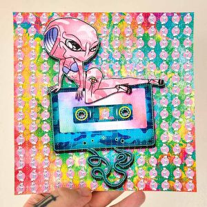 photo of a hand holding alien themed lsd blotter art gift featuring psychedelic rainbow colours and classic audio cassette tape