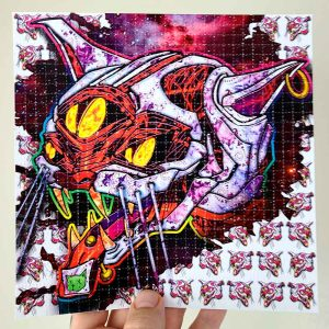 photo of a hand holding LSD blotter acid art print featuring a cat with an acid tab on its tongue