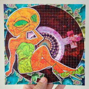 photo of a hand holding alien themed lsd blotter art gift featuring psychedelic colours and fractals
